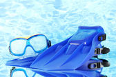Blue flippers and mask on blue sea background — Stock Photo