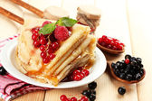 Delicious pancakes with berries, jam and honey on wooden table — Stock Photo