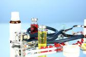Medicamentos y un estetoscopio en un primer plano de fondo azul — Foto de Stock