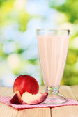 Peach milk shake on wooden table on bright background — Stock Photo