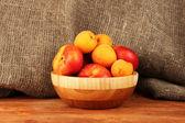Dojrzałe owoce w drewniane miski na płótnie tło zbliżenie — Zdjęcie stockowe