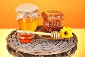 Jar of honey and honeycomb on orange background — Stock Photo