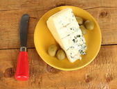 Cheese with mold and olives on the plate and knife on wooden background close-up — Stock Photo