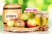 Honey and apples with cinnamon on wicker cradle on natural background — Stock Photo