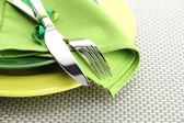 Green empty plates with fork and knife on a grey tablecloth — Stock Photo
