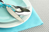 Blue empty plates with fork, spoon and knife on a grey tablecloth — Stock Photo