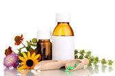 Medicin flaskor med tabletter och blommor isolerad på vit — Stockfoto