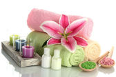 Towels with lily, aroma oil, candles and sea salt isolated on white — Stock Photo