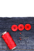 Colorful sewing buttons with thread on jeans isolated on white — Stock Photo