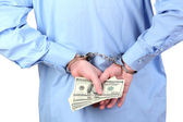 Man in handcuffs is holding dollars, on white background — Stock Photo