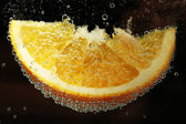 Slice of orange in the water with bubbles, on black background — Stock Photo
