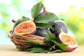 Ripe sweet figs with leaves in basket, on wooden table, on green background — Stock Photo