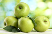 Ripe green apples with leaves, on table, on green background — Stock Photo