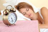 Belle jeune femme dormant sur le lit avec réveil dans la chambre à coucher — Photo