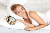 Young beautiful woman sleeping on bed with alarm clock in bedroom — Foto de Stock