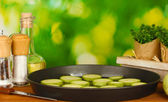 Tranches de courge dans une casserole sur une table en bois le gros plan fond vert — Photo