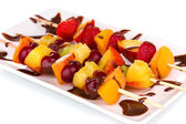 Mixed fruits and berries on skewers with chocolate isolated on white — Stock Photo
