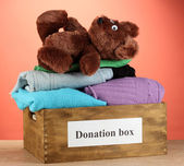 Donation box with clothing on red background close-up — Stock Photo