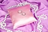 Wedding rings on satin pillow on purple cloth background — Stock Photo