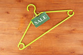 Coat hanger with sale tag on wooden background — Стоковое фото
