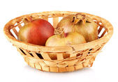 Unripe pomegranates in wicker basket isolated on white — Stock Photo