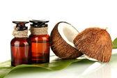 Kokosolja i flaskor med kokosnötter på vit bakgrund — Stockfoto