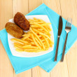 Potatoes fries with burgers on the plate on wooden background close-up — Photo
