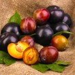 Rip plums on sacking — Stock Photo