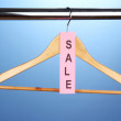 Stock Photo: Wooden clothes hanger as sale symbol on blue background