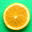 Slice of orange with drop on green background — Stock Photo