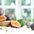 Ripe sweet figs with leaves in basket, on wooden table, on window backgroun — Stock Photo #12646727