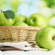 Ripe green apples with leaves in basket, on wooden table, on green backgrou — Stock Photo #12646733