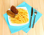 Potatoes fries with burgers on the plate on wooden background close-up — Stock Photo