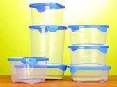 Kunststoffbehälter für lebensmittel auf holztisch auf grünem hintergrund — Stockfoto