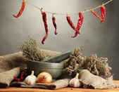 Dried herbs in mortar and vegetables, on wooden table on grey background — 图库照片