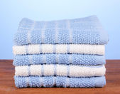 Kitchen towels on wooden table on blue background close-up — Stockfoto