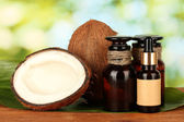Coconut oil in bottles with coconuts on green background — Stock Photo