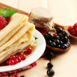 Delicious pancakes with berries, jam and honey on wooden table — Stock Photo #12655001