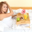 Young beautiful woman in bed with light breakfast on wooden tray — Stock Photo