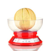 Sweet melon in kitchen scales isolated on white — Stock Photo