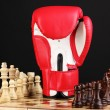 Chess board and boxing glove isolated on black — Stock Photo