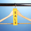 Wooden clothes hanger as sale symbol on blue background - Stock Photo