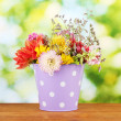 Purple bucket with white polka-dot with flowers on green background — Stock Photo #12704456