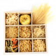 Nine types of pasta in wooden box sections isolated on white - Stock Photo
