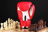 Schachbrett und boxhandschuh isoliert auf schwarz — Stockfoto