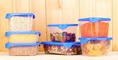 Gefüllte plastikbehälter auf hölzernen hintergrund — Stockfoto