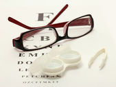 Glasses, contact lenses in containers and tweezers, on snellen eye chart ba — Stock Photo