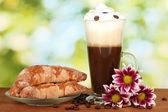 Kieliszek świeżo parzona kawa koktajl i talerzyk z bajgle na jasny zielony backg — Zdjęcie stockowe