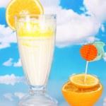 Delicious milk shake with orange on table on sky background — Stock Photo #12712822