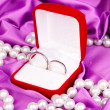 Wedding rings in red box on purple cloth background — Stock Photo